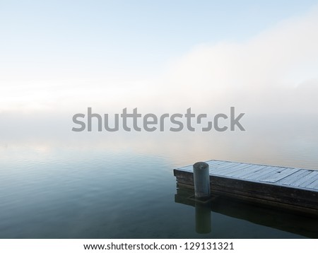 Frosty Fishing Pier in Dense Winter Fog with Pale Blue Sky. - stock photo