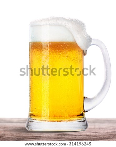 Frosty fresh beer with foam isolated on a vintage wooden table - stock photo