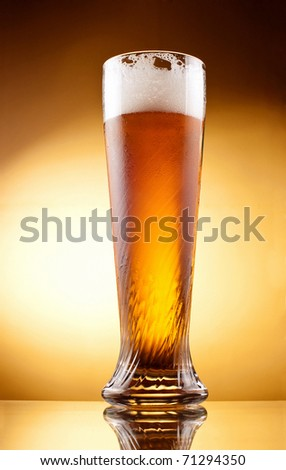 Frosty glass of light beer with froth over yellow background - stock photo