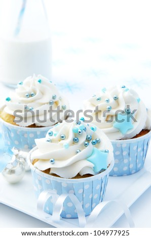 Frosty icy winter xmas theme cupcakes with white icing and blue decorations - stock photo