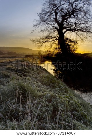 Frosty morning sunrise over country stream