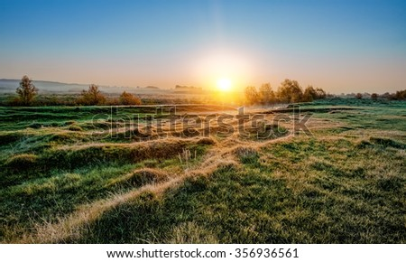 frosty morning sunrise over the river and a field - stock photo