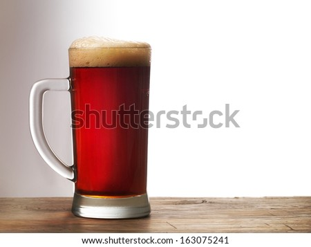 Frosty mug of dark beer on wooden table - stock photo