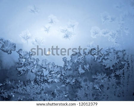 Frosty natural pattern and sun on window glass - stock photo
