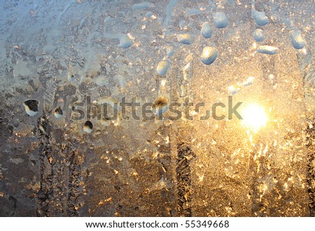 frosty natural pattern and sun on winter glass - stock photo