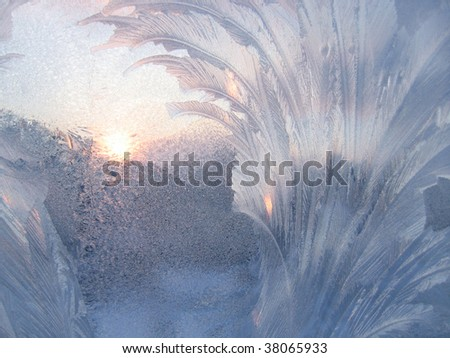 Frosty natural pattern and sun on winter window - stock photo