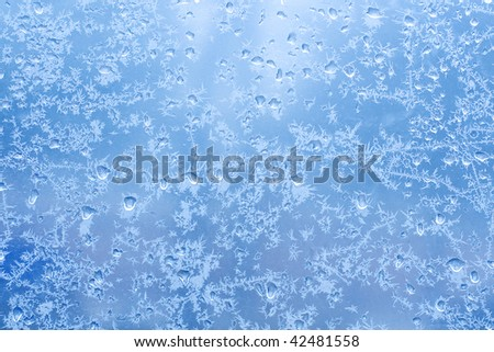 Frosty natural pattern on winter glass with drops - stock photo