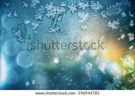 Frosty pattern at a winter window glass with sunlight. Light background. - stock photo