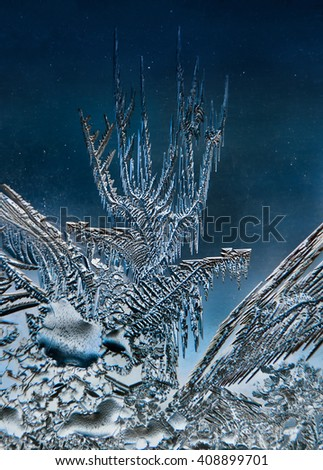 Frosty pattern in daylight obtained at low temperature on the window glass. - stock photo
