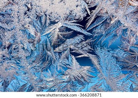 frosty pattern on blue frozen window glass - stock photo