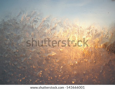 Frosty pattern on glass winter window and Sun