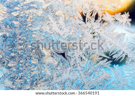 frosty pattern with sunlight on frozen window - stock photo