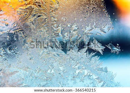 frosty pattern with sunlight on frozen window glass - stock photo