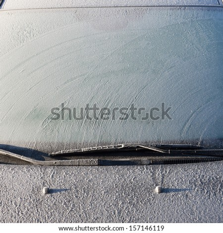Frosty patterns on a completely covered car windscreen - stock photo