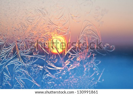 Frosty patterns on the window pane at sunset. Focus are in center. - stock photo