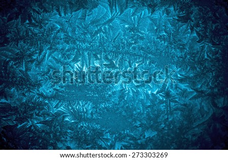Frosty patterns on winter window, blue toning background. - stock photo