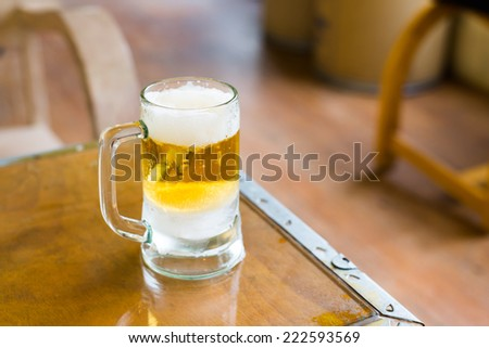 Frosty pint glass of beer on wooden table - stock photo