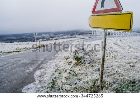 Frosty road sing in front of the frozen grass field