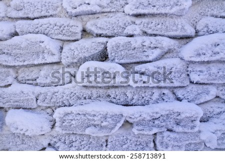 Frosty stone wall - abstract winter background - stock photo