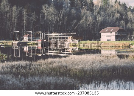 Frosty winter lake illuminated by the rising sun. house. - retro, vintage style look - stock photo