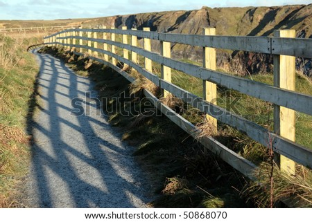 frosty winters view at ballybunion cliff side walk with atlantic view and fence shadows - stock photo