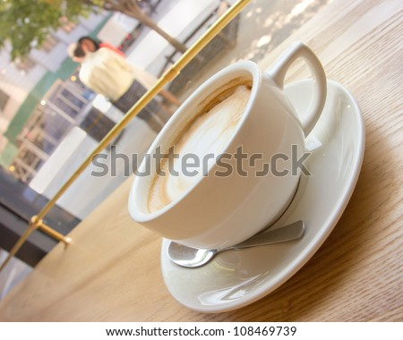 Frothy cup of cappuccino with young couple in the background in view - stock photo