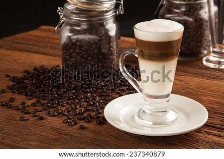 Frothy, layered cappuccino in a clear glass mug - stock photo