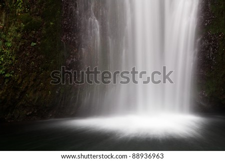 Frothy misty bottom of a waterfall falling into a dark pool of water - stock photo