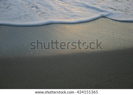 Frothy Water Rising Up the Beach - stock photo