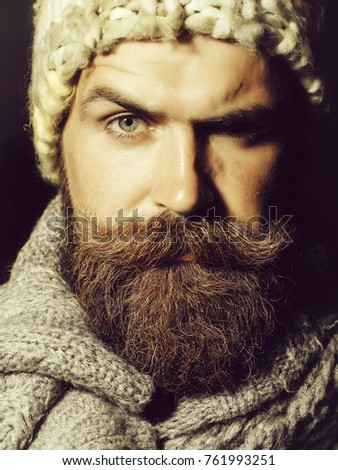 Frown bearded man with beard and moustache stylish hipster male in warm knitted hat and coat outdoors on dark background