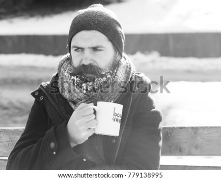Frown man, bearded hipster with beard and moustache covered with white frost drinks from cup with good morning text sitting on wooden bench on snowy winter day outdoors on natural background