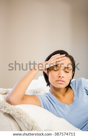 Frowning brunette with hand on face on the sofa
