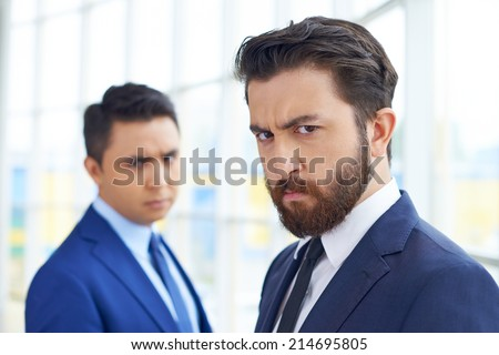 Frowning businessman looking at camera on background of his displeased colleague - stock photo