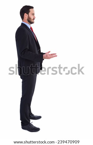 Frowning businessman presenting with hands on white background - stock photo