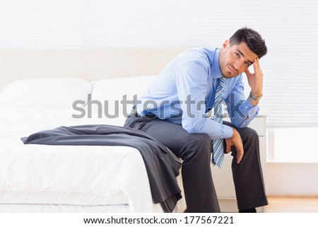 Frowning businessman sitting at edge of bed looking at camera at home in bedroom