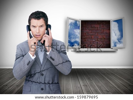 Frowning businessman wrapped in cables phoning in front of blocked window - stock photo