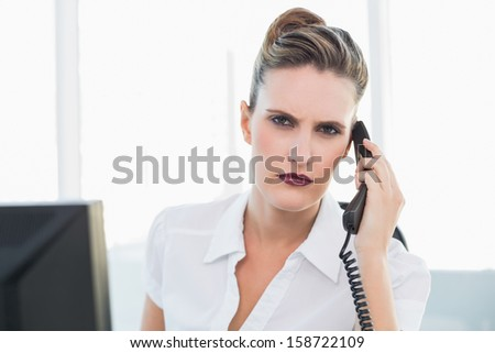 Frowning classy businesswoman talking on the phone in bright office - stock photo