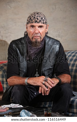 Frowning gang member in leather vest in cold stare