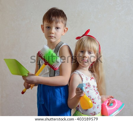 Frowning girl and boy holding iron and broom with upset expression for being forced to do household chores - stock photo