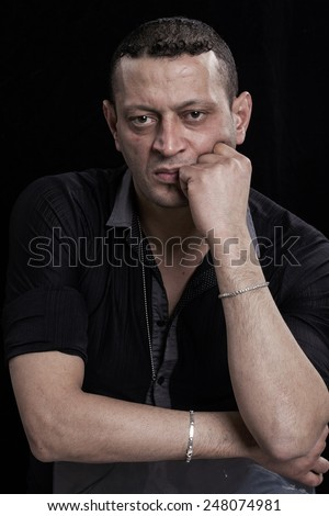 Frowning man portrait looking at camera on black background - stock photo