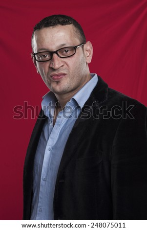 Frowning man portrait wearing glasses on red background - stock photo
