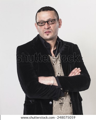 Frowning man with crossed arms wearing glasses - stock photo