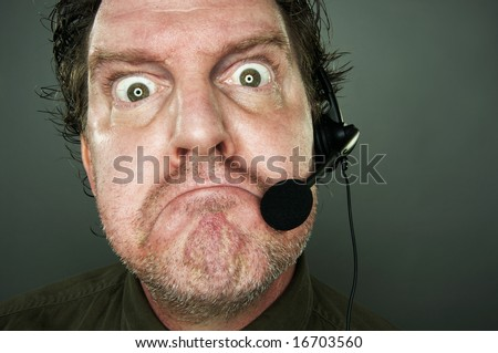 Frowning man with telephone headset. - stock photo