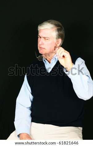 frowning older man looking at eyeglasses on black background