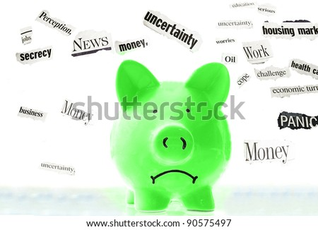 frowning pink piggy bank with bad economic news headlines - stock photo