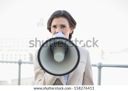Frowning stylish brown haired businesswoman using a megaphone outdoors
