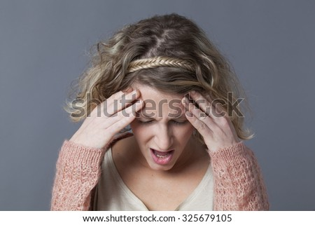 frowning young blond woman shouting in holding her head for headache or concentration problems