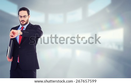 Frowning young businessman checking time against bright white room with windows - stock photo