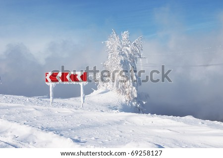 Frozen and snowed guide road sign of turn and tree in a blue foggy background - stock photo
