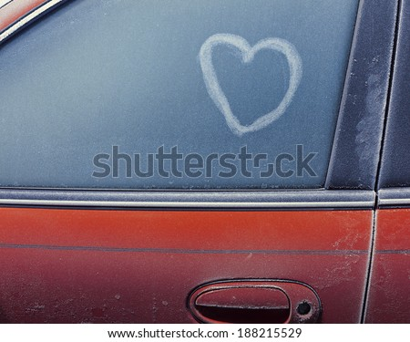 Frozen automobile window with heart - stock photo